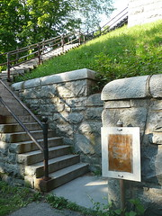 Stairs to the bridge, with weathered sign