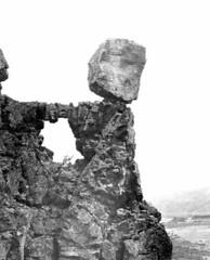 Balanced rock resting above lava arch near Par...