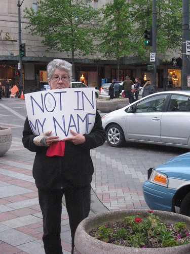 An older white woman stands holding a poster that says 'Not in my name' in capitals.