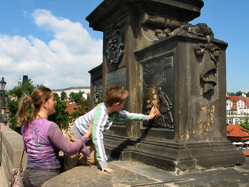 A boy touching the relief of the statue of St. John of Nepomuk for good luck by you.