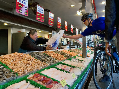 A bicyclist picks up some fresh seafood from the Maine Avenue Fish Market.