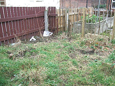 Before - Bed 3 - the fruit bed. the rubbish has gone from this area but it needs working over, weeding, the plants cared for, straw around the strawberries replaced and the plants fed.