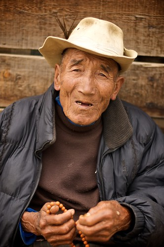 An elderly Tibetan man poses for a portrait while he counts with his prayer beads in Litang, China.