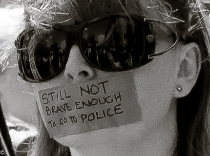 A pale-skinned dark-haired woman wearing sunglasses has a large piece of tape covering her mouth.  On the tape is written STILL NOT BRAVE ENOUGH TO GO TO POLICE