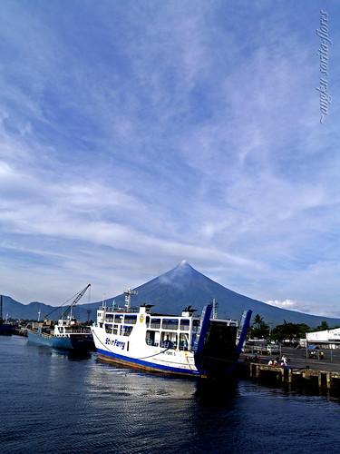 a volcano, a boat at a port