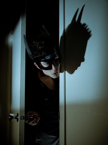 young man with spiky hair and Dark Knight mask on pokes head through doorway of dark house