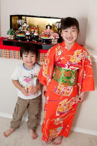 Brother and sister posing in front of their Hina Matsuri (Girls' Day) display