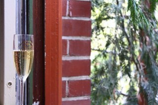 A nearly full glass of champagne on a windowsill with red brick wall.