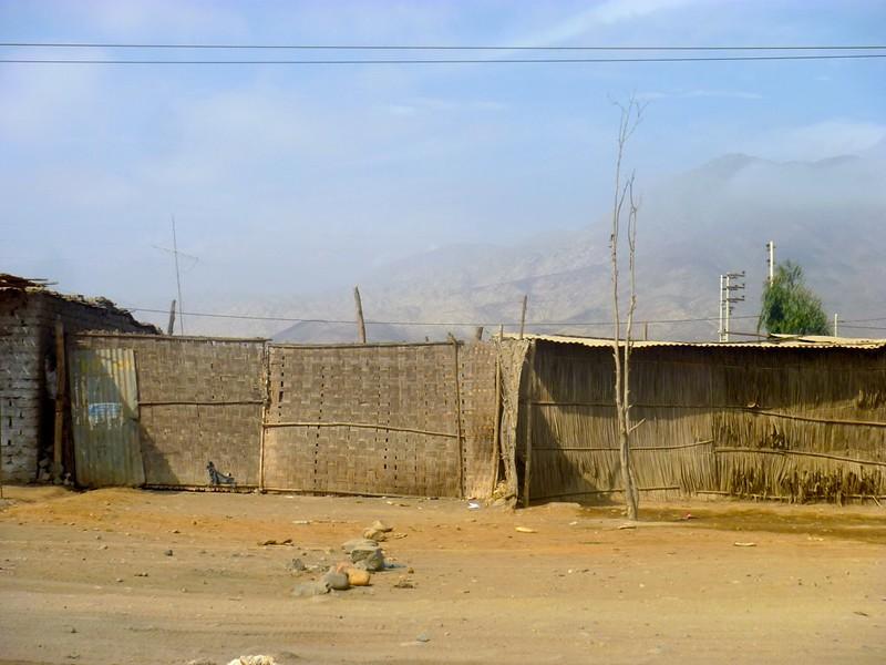 Bastmatten- und Lehmziegelhütten am Straßenrand