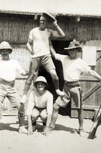 4 soldiers outside hut