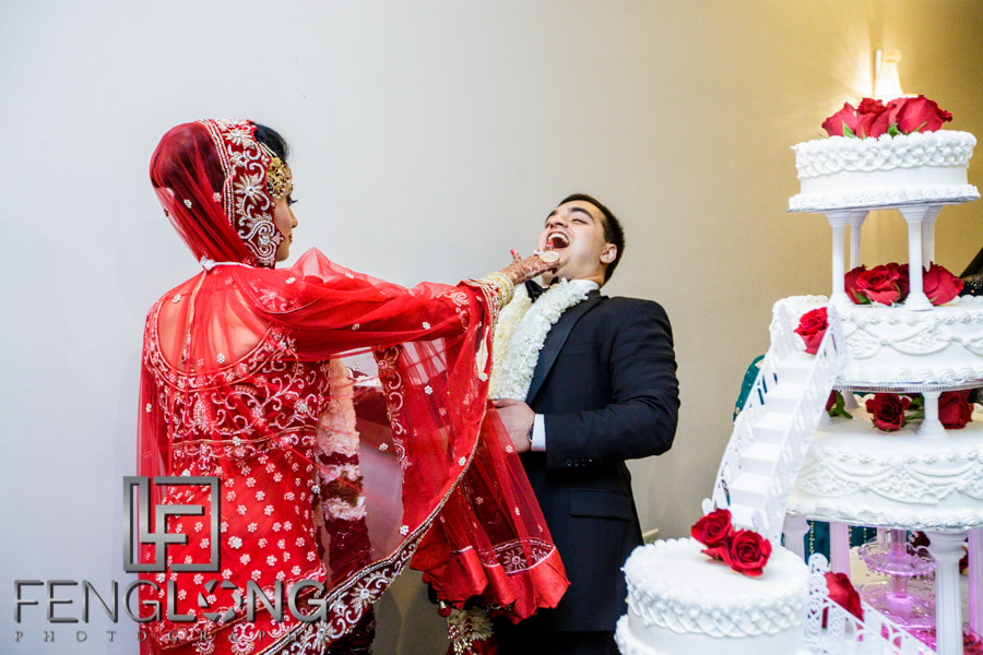 Bride putting cake on groom's face