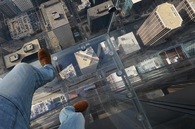 Pies sobre el avismo del mirador skydeck de la Willis Tower de Chicago