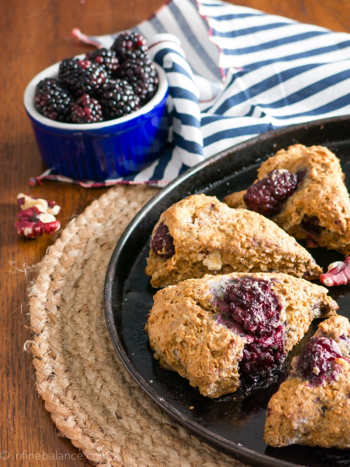 blackberry and walnut scones on a baking tray, blackberries in the background