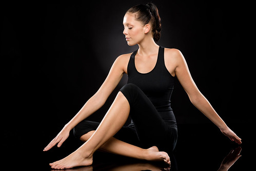 Young woman performing yoga with stretched arms by CandyBoxImages