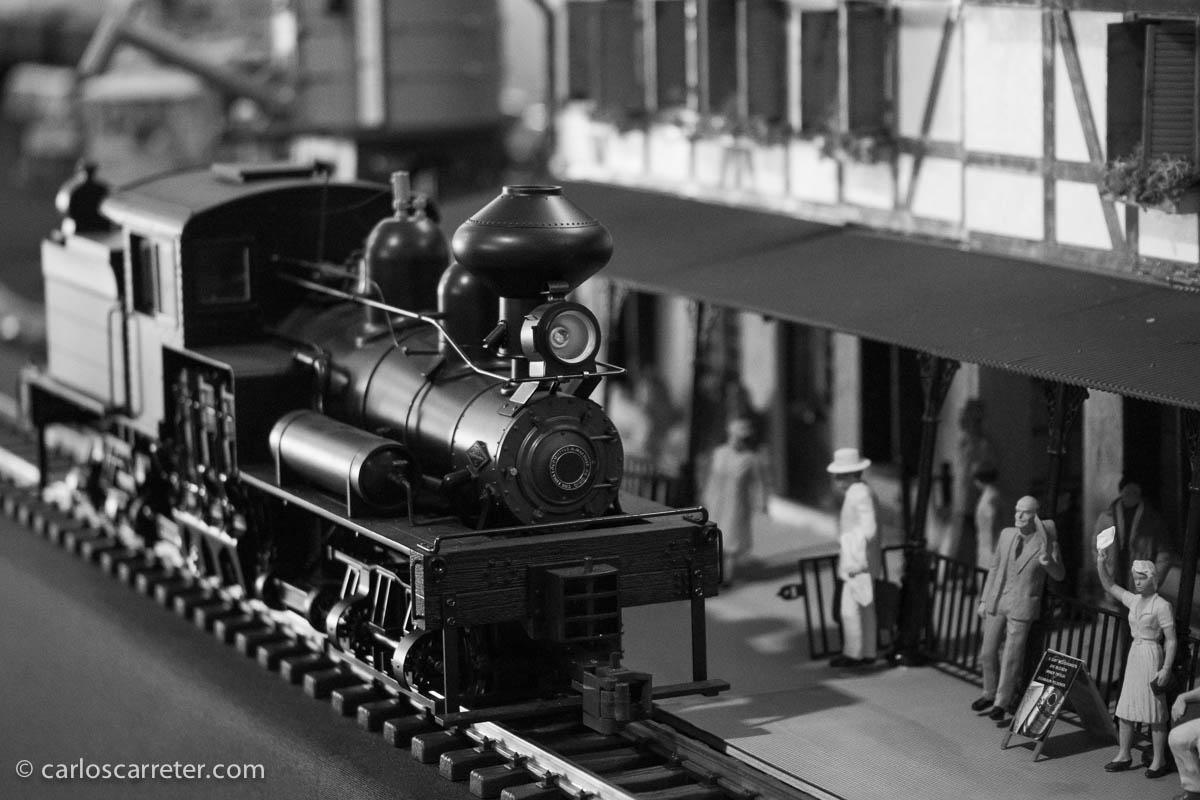 La locomotora de vapor atraviesa la estación ante la mirada de los viajeros que esperan