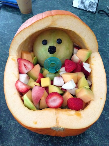 Pumpkin baby carriage with sliced fruit and a cantaloupe baby-head