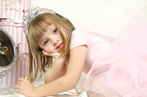 princess little girl painting makeup lipstick on the mirror