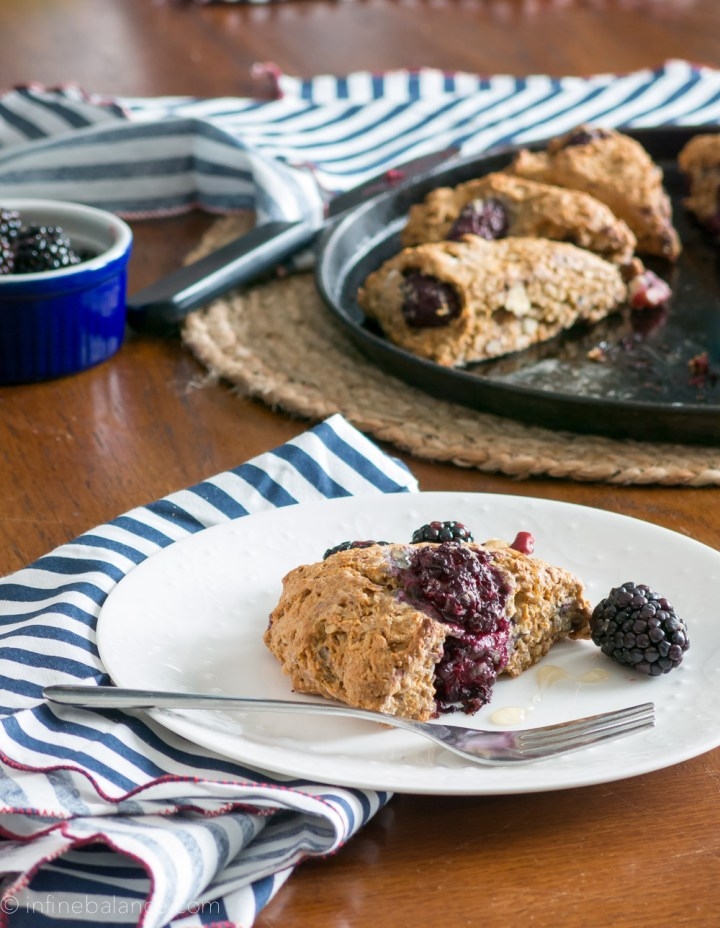 blackberry scone on a plate with baking try of scones in background