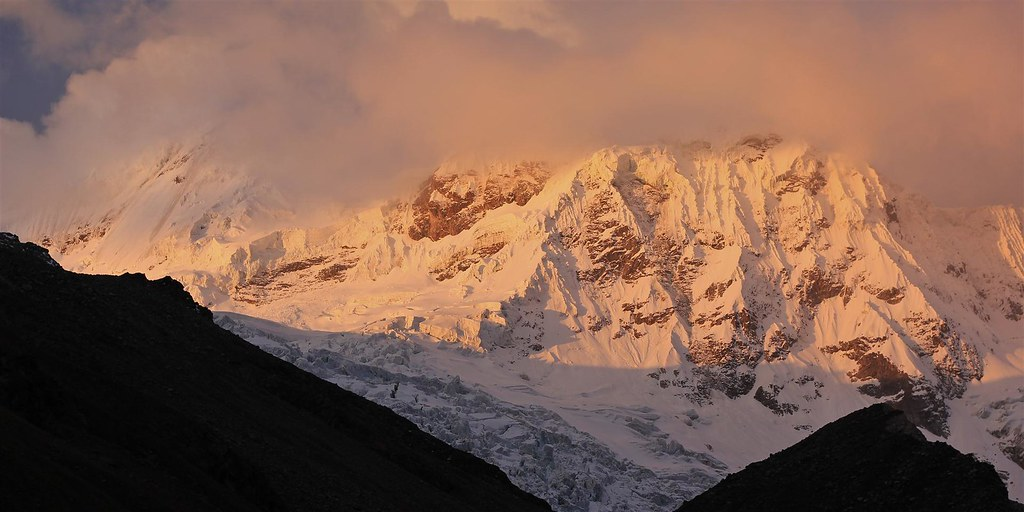 Alpenglow on the cloudy, fluted west wall of Tocllaraju (left, 6032m). The aim was to climb to high camp the next day. Once again bad weather would set in and ruin our plans. Cordillera Blanca. Peru.