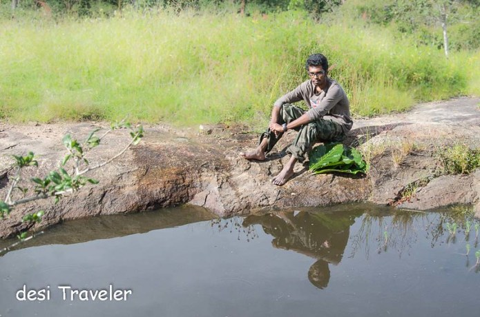 An Eco Volunteer rests next to water hole Bandipur