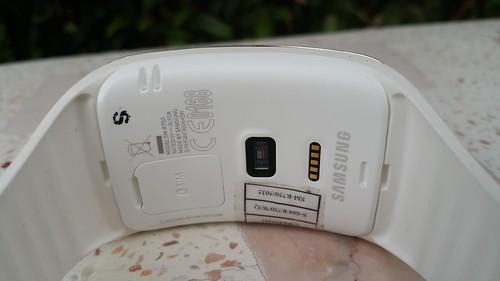 ด้านหลังของ Galaxy Gear S มีช่องใส่ Nano SIM card, เซ็นเซอร์วัดอัตราการเต้นหัวใจ และขั้วทองเหลืองสำหรับชาร์จแบตเตอรี่