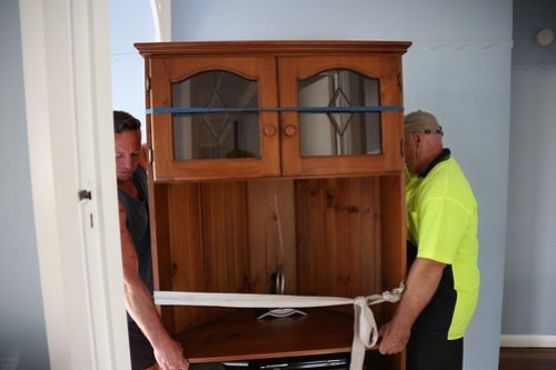 Movers lifting display cabinet through house image.