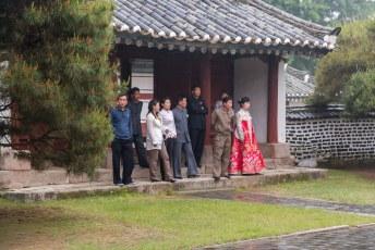 Het gezelschap kijkt toe terwijl bruid en bruidegom poseren.