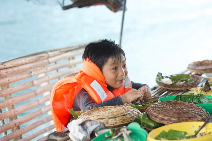boy enjoying the food in the Lake Pandin bamboo raft