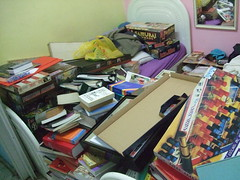 bedroom piled up with books and games