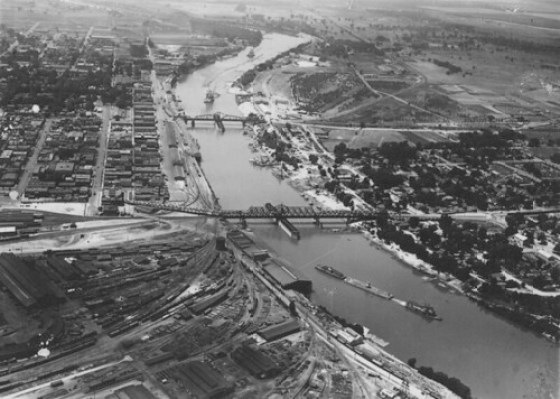 Looking south over Sacramento River with I and M Street Bridges in view, Southern Pacific Rail yards in foreground, Sacramento, CA, ca. 1930