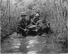 Soldiers carry a wounded comrade through a swa...