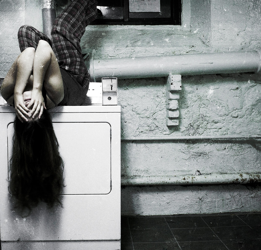 Image of girl in awkward position covering her head with her hands.
