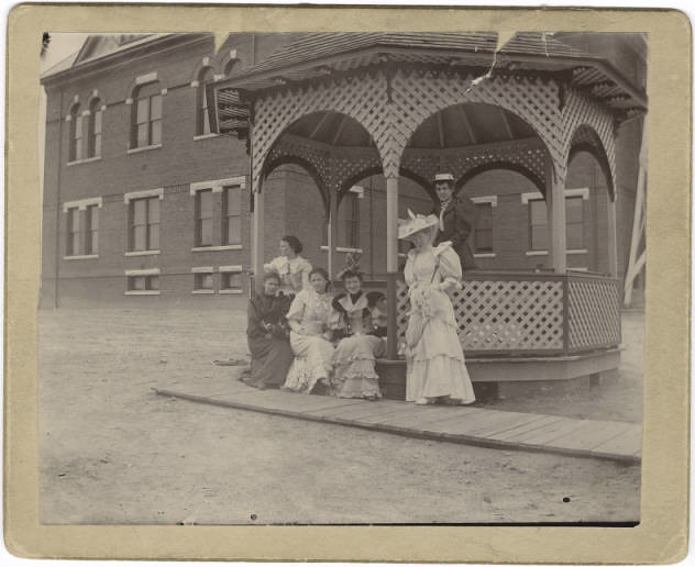 Six students pose at the Gazebo located between Main Building and Brick Dormitory in 1893.