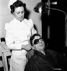 Female nurse Cecile Dumas bathes and dresses workman Tom Heard's eye at the Arvida Aluminum Company of Canada