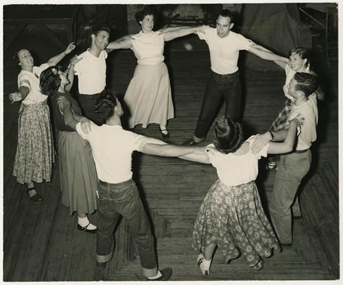 Young men and women dancing in a circle, circa 1950