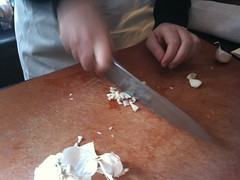 Slicing a smashed clove of garlic