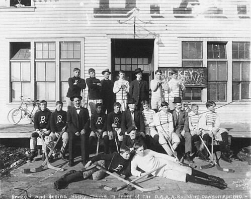 Renzoni and Regina hockey teams posed with their equipment in front of the Dawson Amateur Athletic Association building