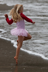 Cute Little Girl in Pink Dances on  Beach duri...