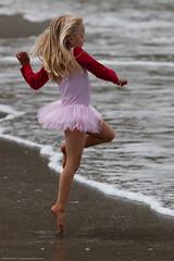 Cute Little Girl in Pink Dances on  Beach duri...