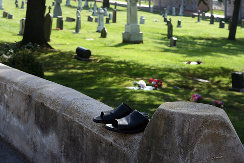 Shoes in front of a row of graves