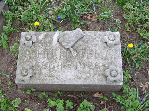 """Rectangular grave stone with an open flower in each corner and a hand in the top center clutching a tool, possibly a brush.  The stone reads """"John Hoffman, 1868-1926"""""""
