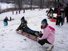 Victoria prepares to give Hooper a push-off on his first-ever day of sledding, 12/19/09.