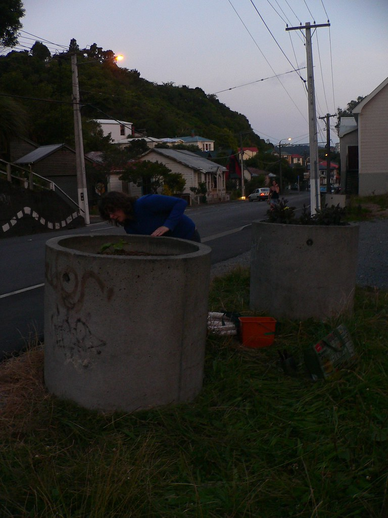 Shows the tubs and a person reaching around them in the dusk.