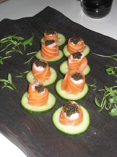 Salmon sashimi with caviar, served on a cucumber crisp.