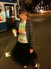 A photo of at a tram stop in Zurich, holding a Starbucks cup and grinning like a loon. I'm wearing a black petticoat and a t-shirt that says 'party like a popsong from the 80s'.