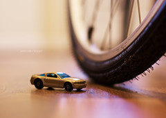 on a wooden floor there is a toy car, looming over it is a bicycle wheel