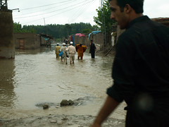 People wade through flooded streets in Charsad...