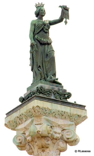 En lo alto del Monumento a los Fueros, en el Paseo de Sarasate, una matrona que simboliza a Navarra sostiene los Fueros en su mano.