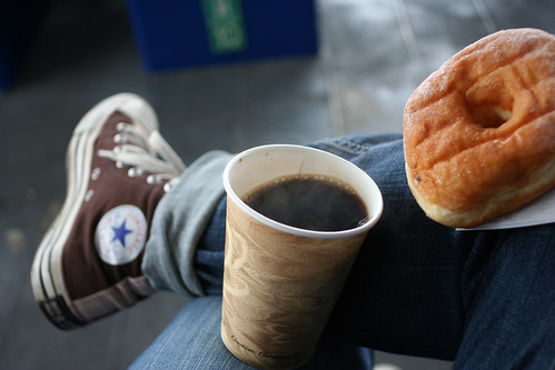 Coffee and doughnut in lap, with Chuck-clad foot in background