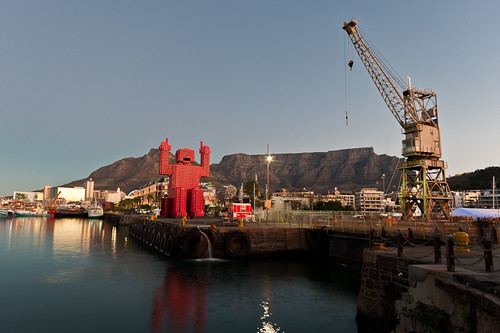 A Coca-Cola crate statue and a dockyard crane 'face off' in the V&A Waterfront with Table Mountain in the background